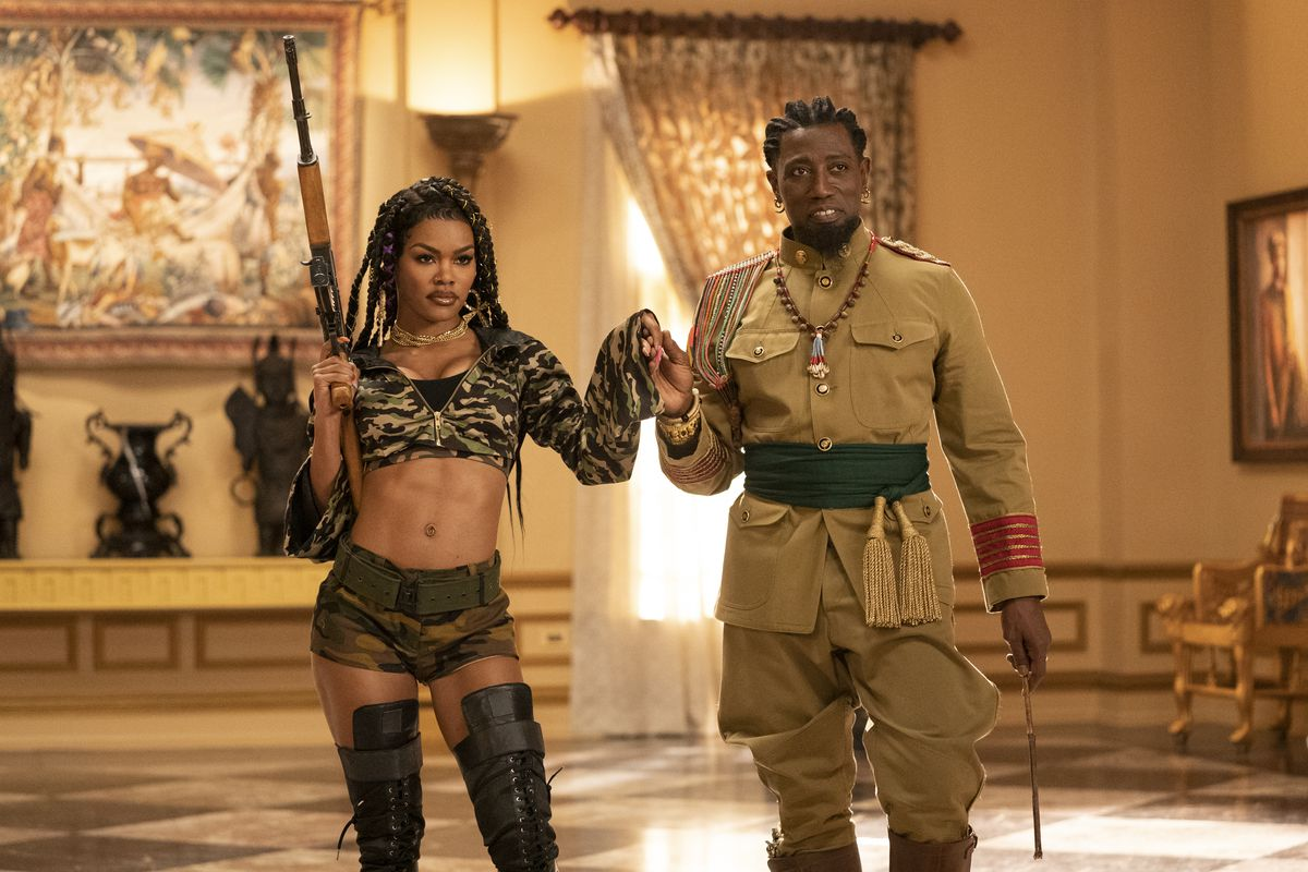 Teyana Taylor, holding a rifle and wearing a belly-baring camo outfit, holds Wesley Snipes' hand in Coming 2 America