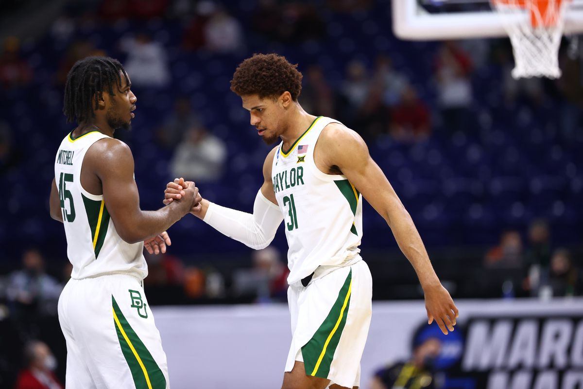 Davion Mitchell and MaCio Teague of the Baylor Bears clasp hands late in the game against the Arkansas Razorbacks in the Elite Eight round of the 2021 NCAA Division I Men's Basketball Tournament held at Lucas Oil Stadium on March 29, 2021 in Indianapolis, Indiana.