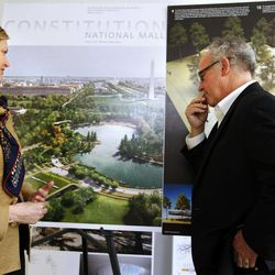 In this photo taken Thursday, April 5, 2012, Caroline Cunningham, President of the Trust for the National Mall, left, and Donald Stastny, an architect advising the trust, look at two of several proposed designs for overused and neglected areas of the National Mall in Washington.