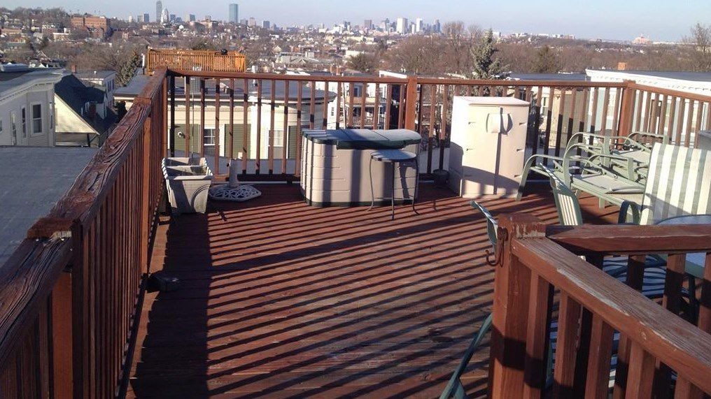 A small roof deck with two storage compartments and some chairs, and there's a city skyline in the distance.
