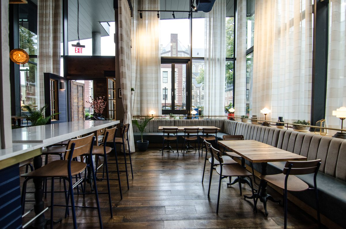 A high-ceilinged restaurant interior features a wooden floor, wooden tables and chairs, off-white banquettes and accents, navy blue accents, and sheer white curtains over the windows. A high-top table is in the mix, with a white top.