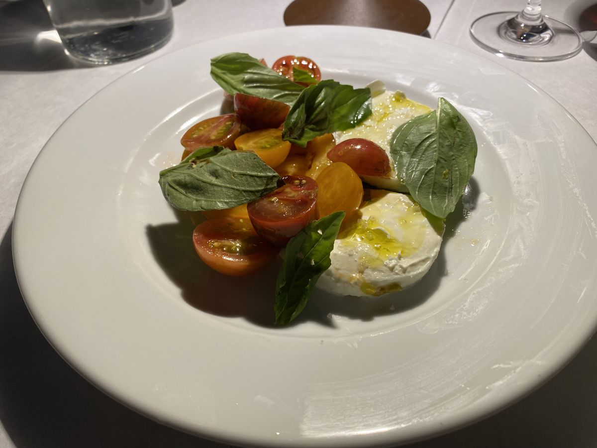 Red and orange tomatoes sit adjacent to fresh mozzarella drizzled with olive oil; verdant basil leaves also garnish the preparation.