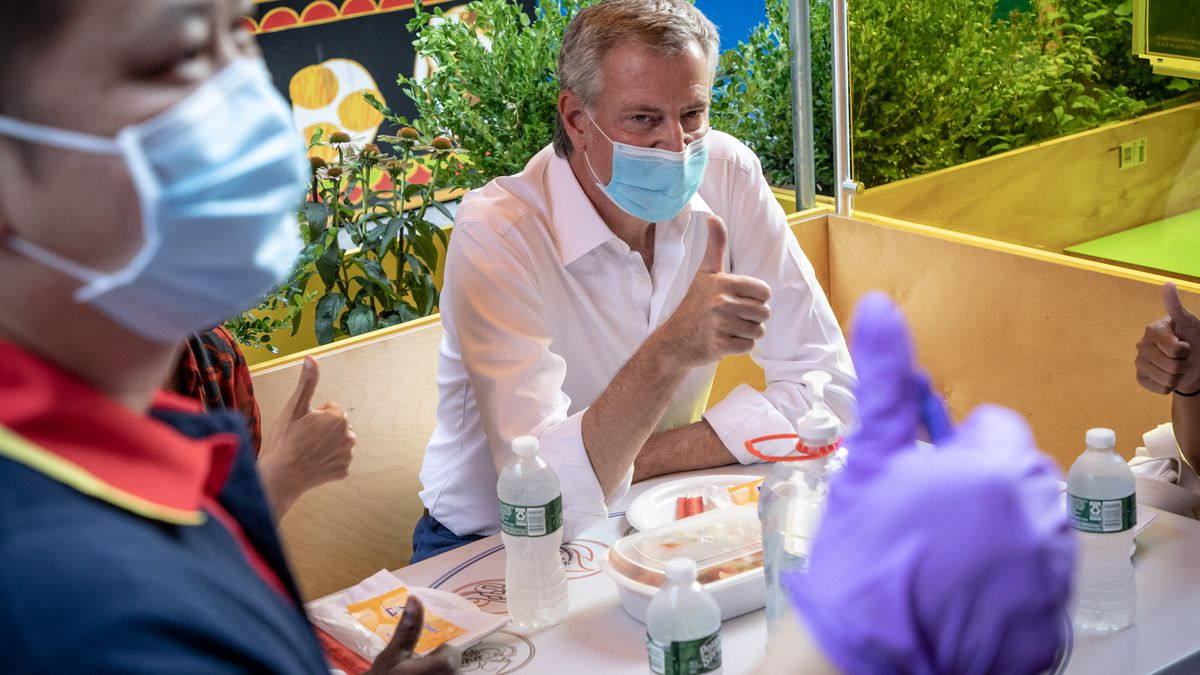 NYC Mayor Bill de Blasio sits at a table at a colorful outdoor seating area wearing a mask and gives the thumbs up