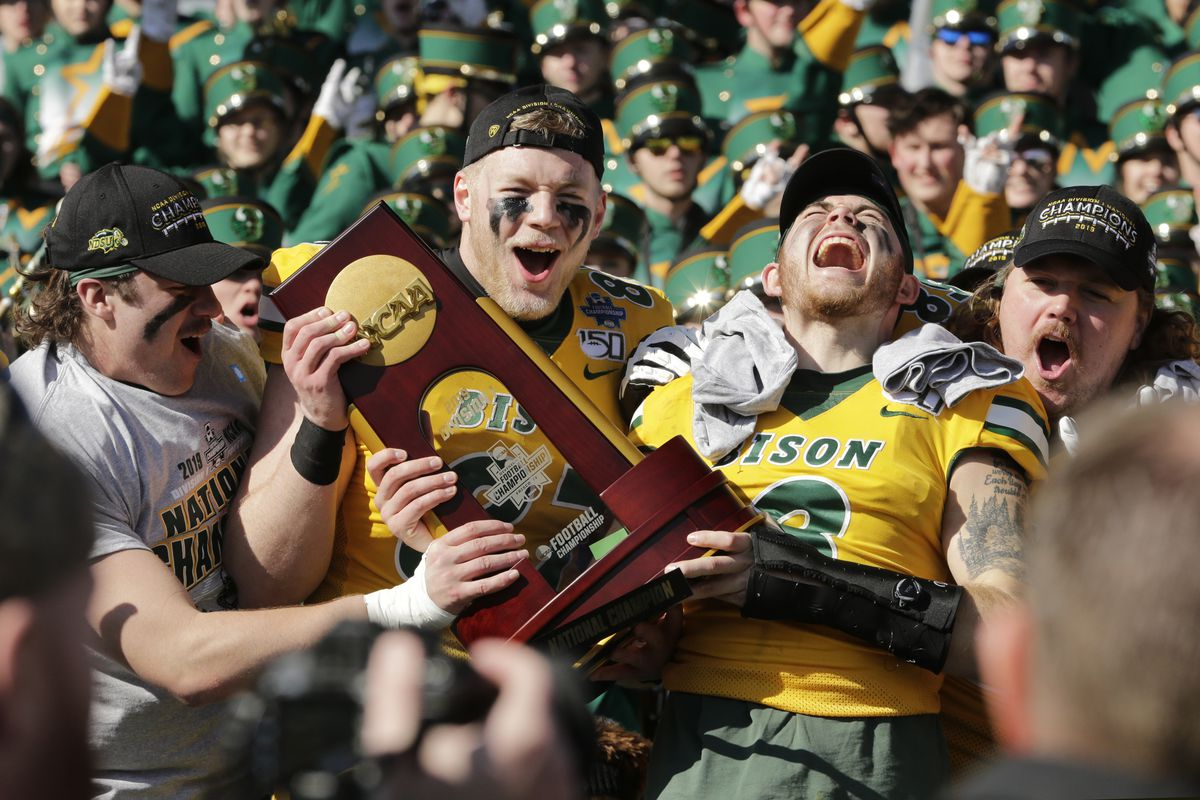 North Dakota State Bison tight end Noah Gindorff and North Dakota State Bison linebacker Jaxon Brown celebrate with the trophy after the game against the James Madison Dukes at Toyota Stadium.
