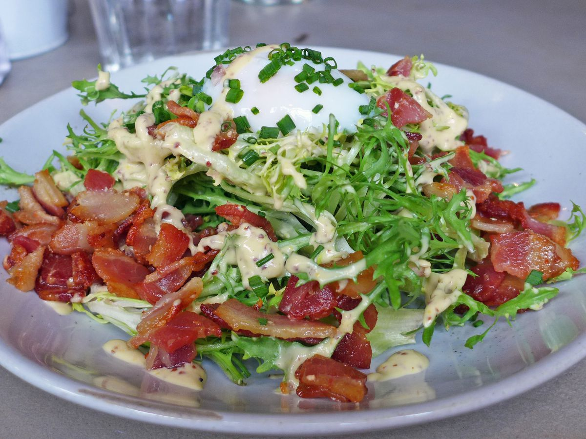 A salad of chickory with an egg on top and loads of bacon and greens around the periphery.