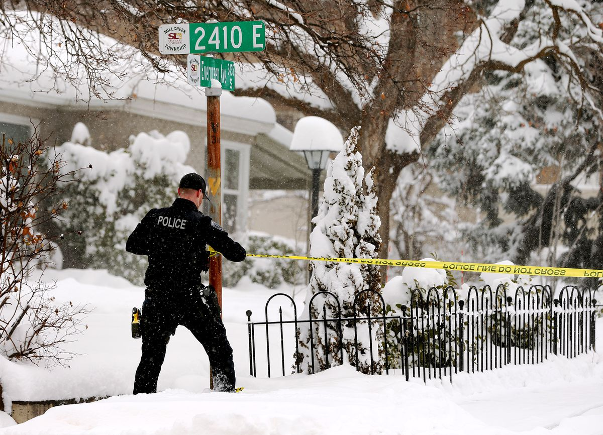 """A Unified police officer puts up police tape after a 56-year-old man with a gun was shot and killed by police during a """"domestic incident"""" at 2468 E. Evergreen Ave. (3400 South) in Millcreek on Monday, Feb. 3, 2020."""