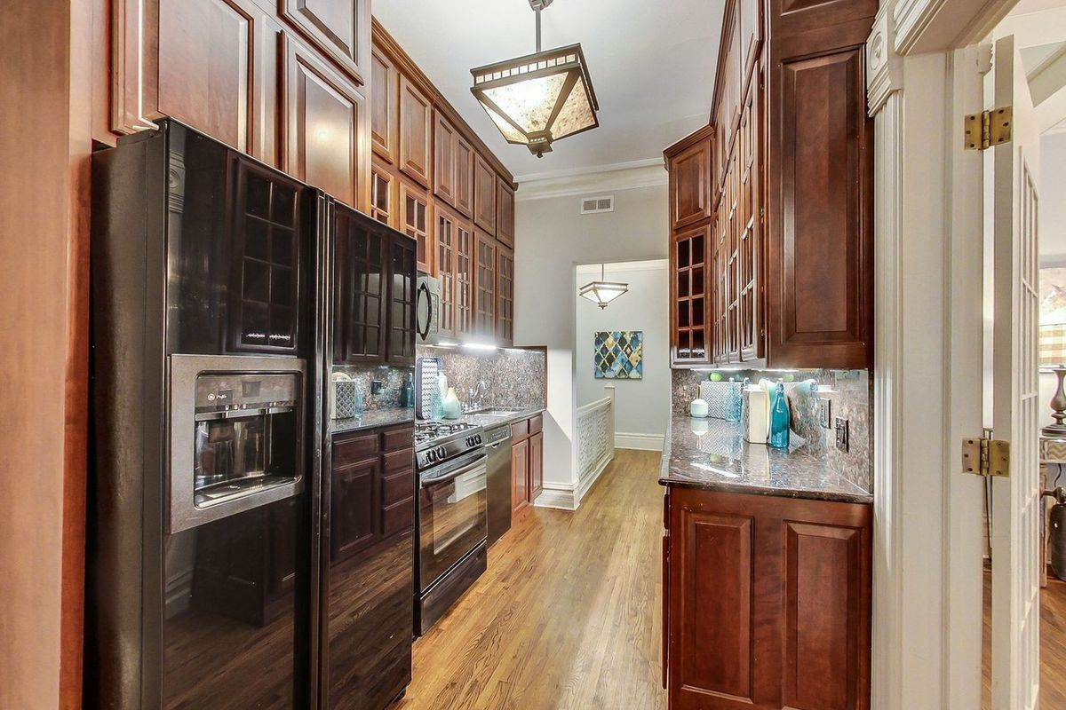 A kitchen with red wood cabinets and granite counters on both sides. There are black appliances and hardwood floors.