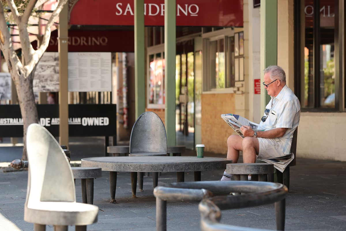 A man reads a local newspaper while sitting on roadside seating on South Terrace on March 26, 2020 in Fremantle, Australia.