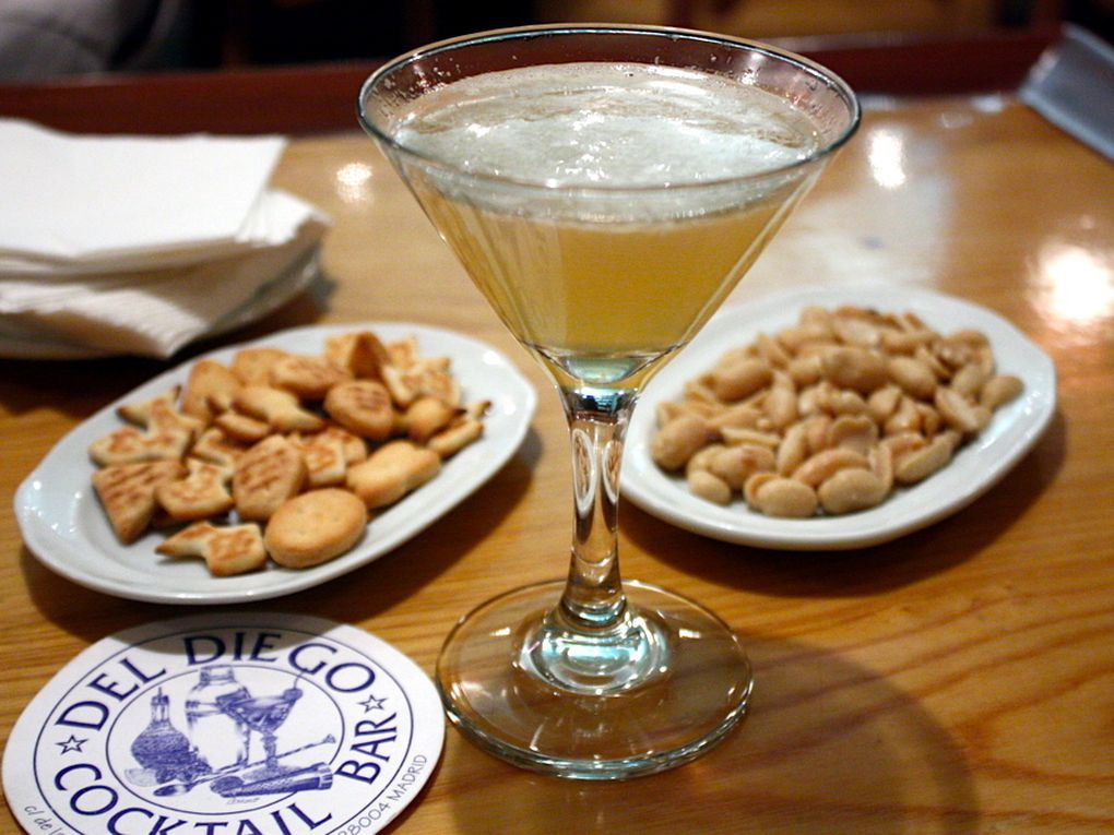 A cocktail in a martini glass sits in the middle of several small plates of crunchy snacks and a coaster branded with the logo of Del Diego Cocktail Bar.