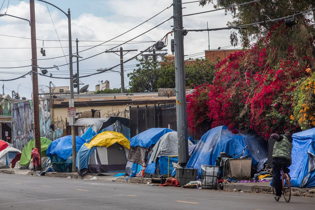 Blue, yellow, and grey tents line a sidewalk and abut a metal fence draped in pink and orange flowering vines. Power lines hang overhead.