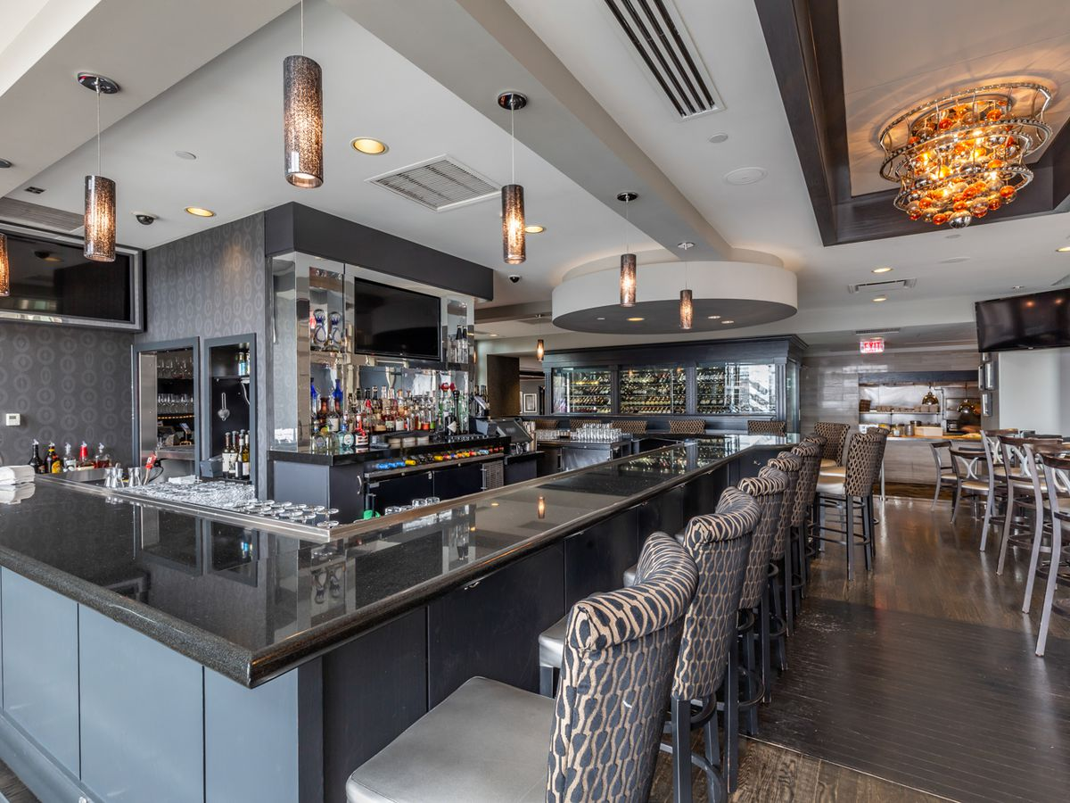 Interior shot of the bar at Morton's the Steakhouse, with a light gray motif and a distinctive orange light fixture.