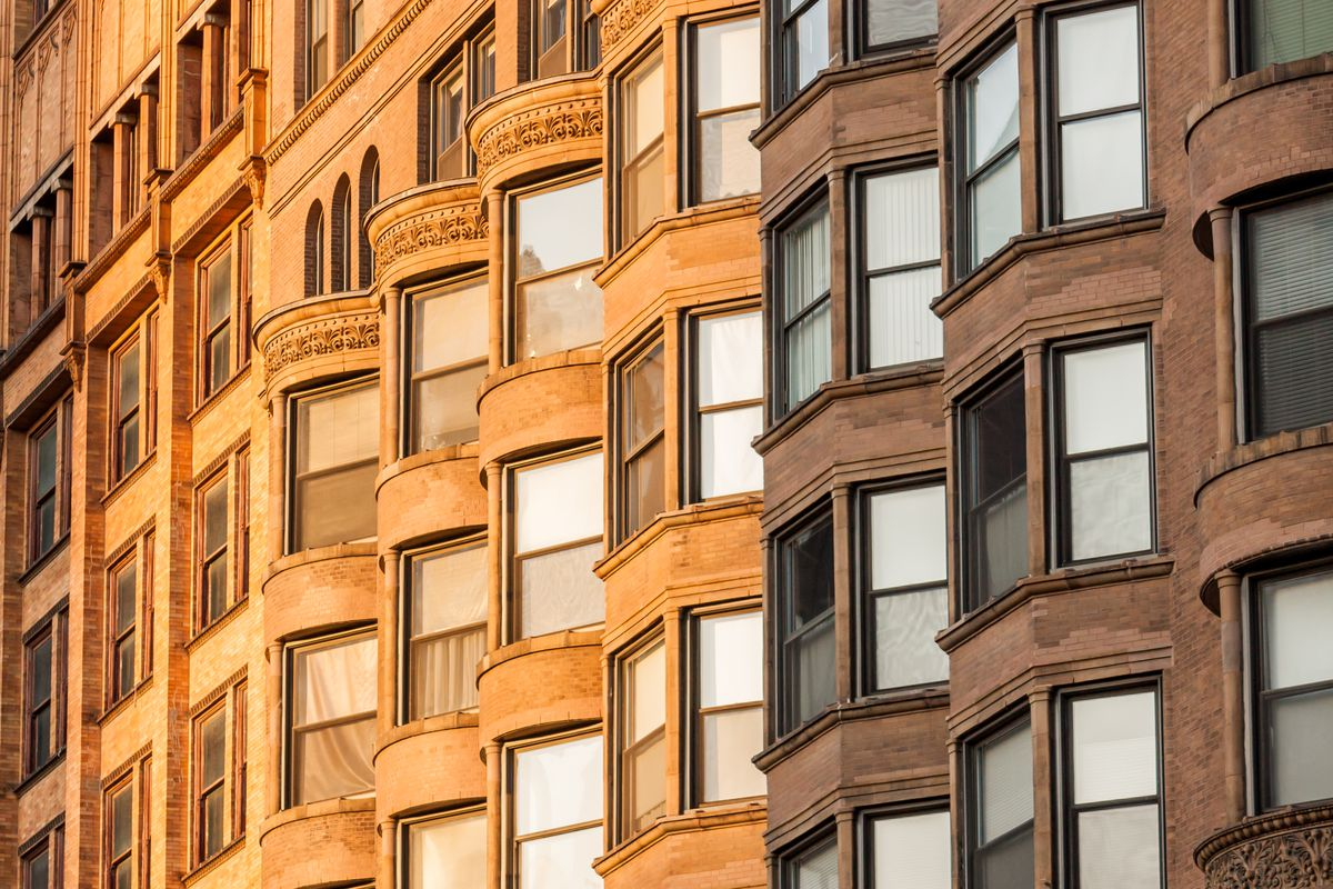 A view of apartment windows with sunlight on them.