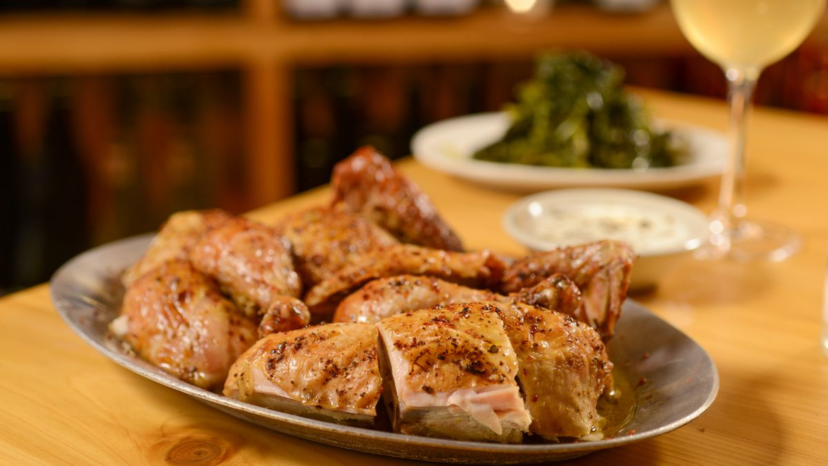 A plate of roast chicken sits on a light wood table next to a glass of white wine
