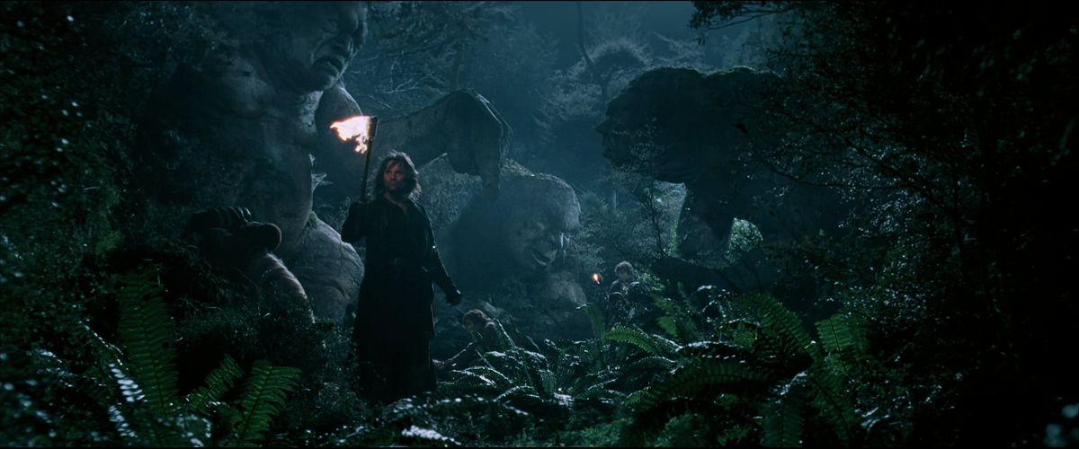 Ο Άραγκορν κρατά έναν πυρσό μπροστά από τρία τρολ που έχουν παγώσει στην πέτρα στο Fellowship of the Ring.
