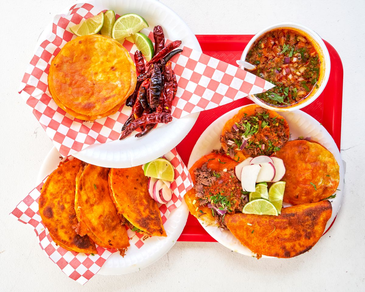 Tacos, quesadillas, and more on white styrofoam plates with a red tray at Teddy's Red Tacos.