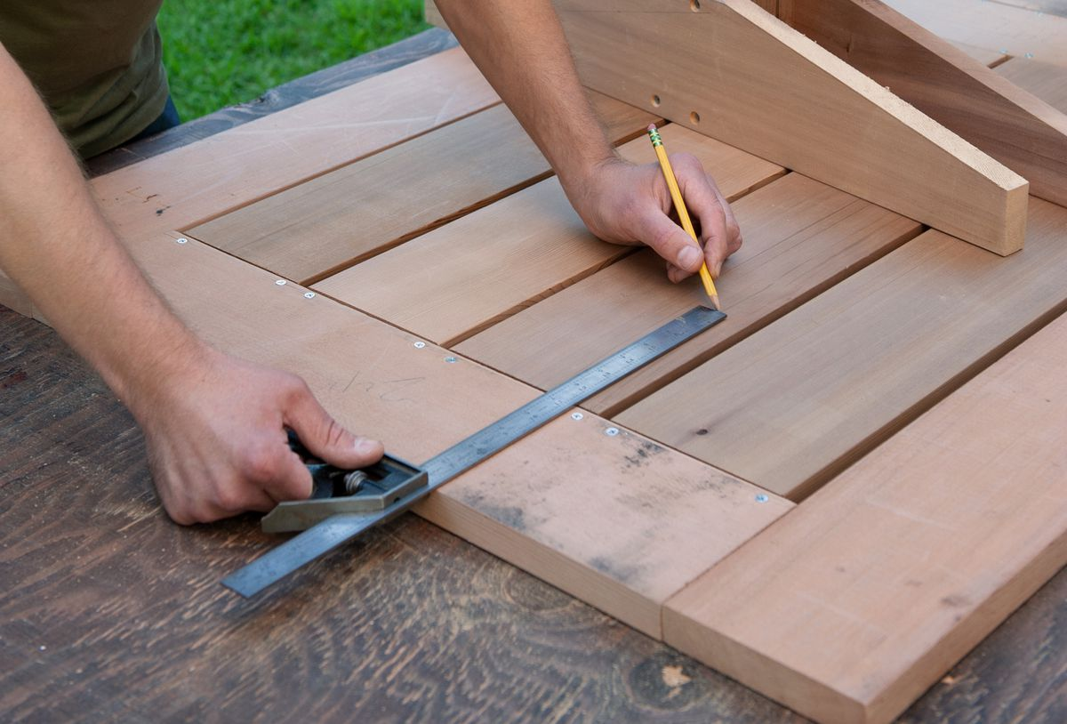 Man Finds Center Of Picnic Table Base Using Combination Square