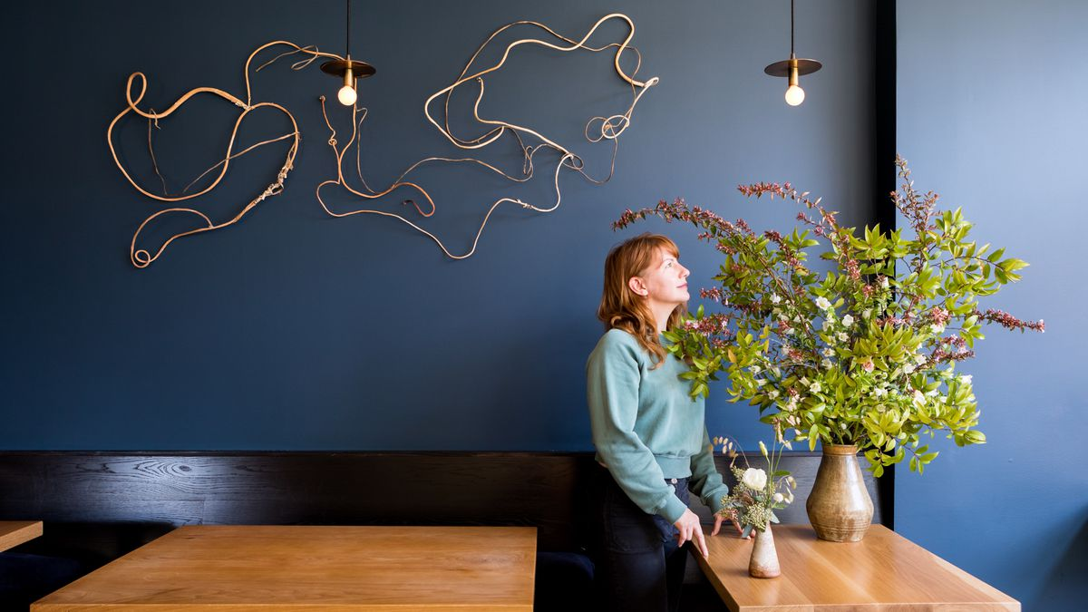 Rebekah Northway of the Petaler stands under a seaweed wall installation and a next to a floral arrangement at Octavia restaurant.