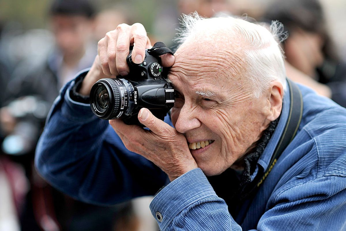 Fashion photographer Bill Cunningham taking a photo