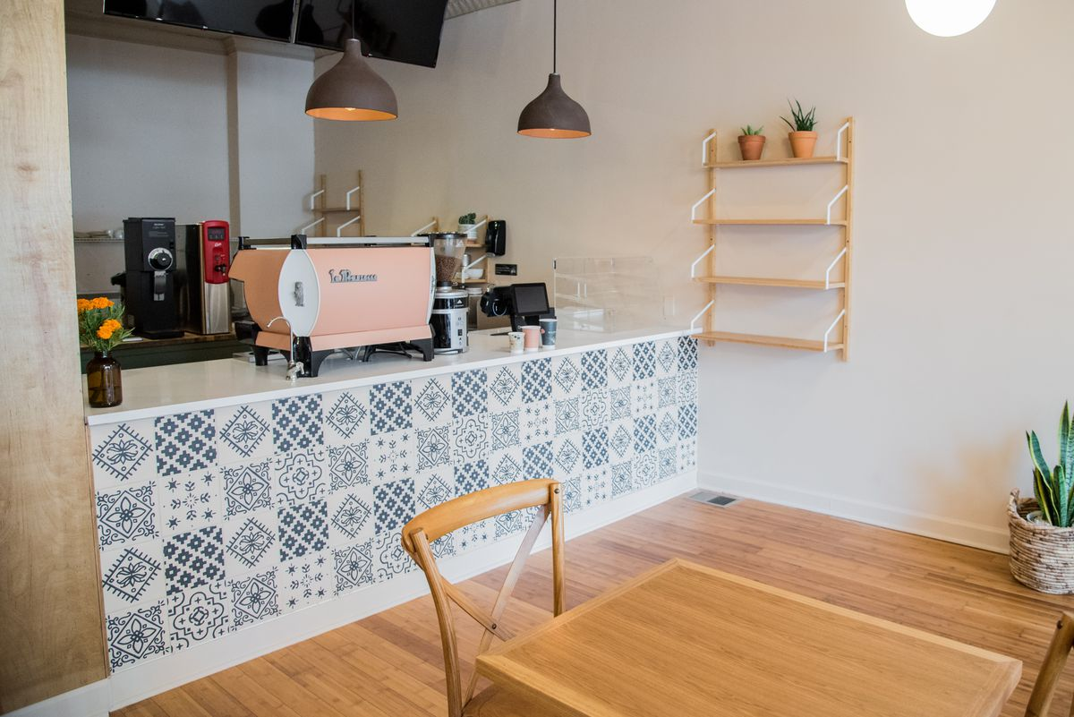 A coffee bar covered with white tiles with blue prints, and a pink espresso machine.