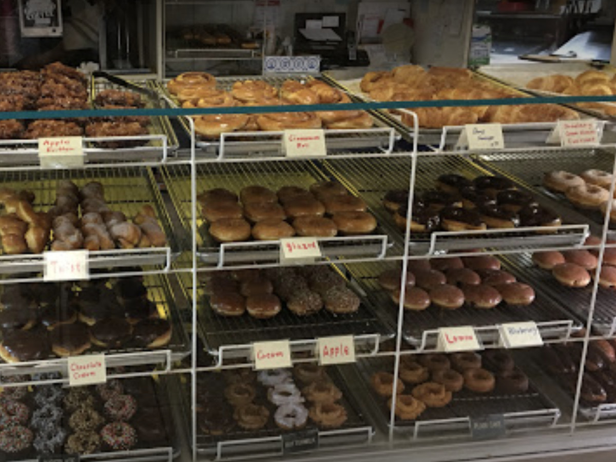 Racks of doughnuts, from cruellers to glazed to colorful sprinkled versions, at Dona Queen in Seattle