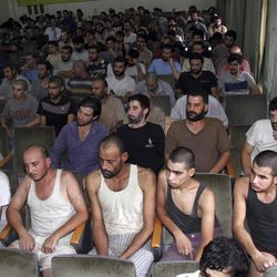 Syrian prisoners sit in a courtroom before their release in Damascus, Syria, Saturday, Sept. 1, 2012. Syria's official state news agency, SANA reported Saturday that 225 detainees, who took part in anti-government protests, were released. The amnesty by authorities is the second in a week as some 378 prisoners from Damascus and the central province of Homs, were freed on Monday. Rights activists say tens of thousands of Syrians have been detained over the past 18 months.