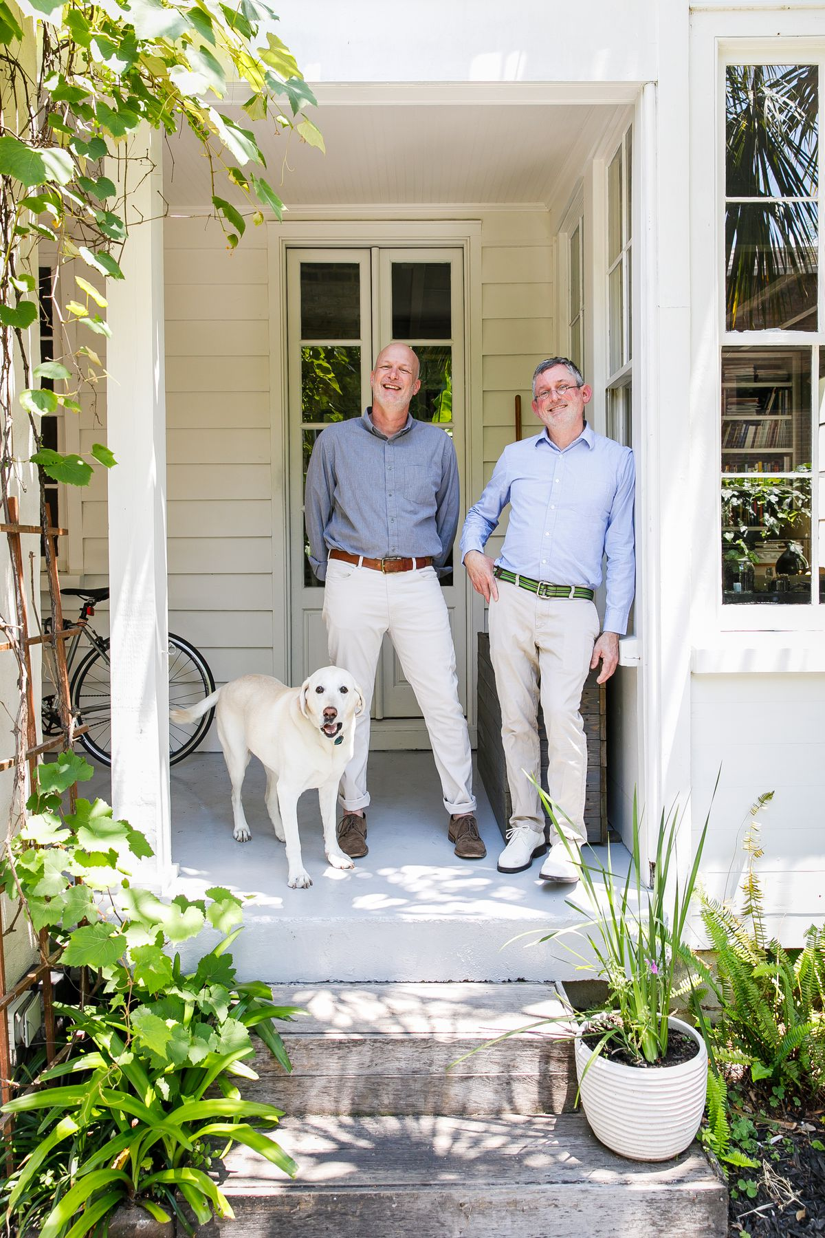 The homeowners and their white dog stand on the porch of their house.