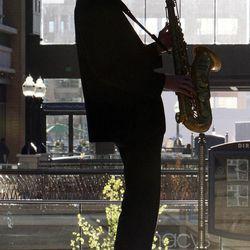 Stephen Tobian plays saxophone on the skybridge at City Creek Center in Salt Lake City, Thursday, March 22, 2012.