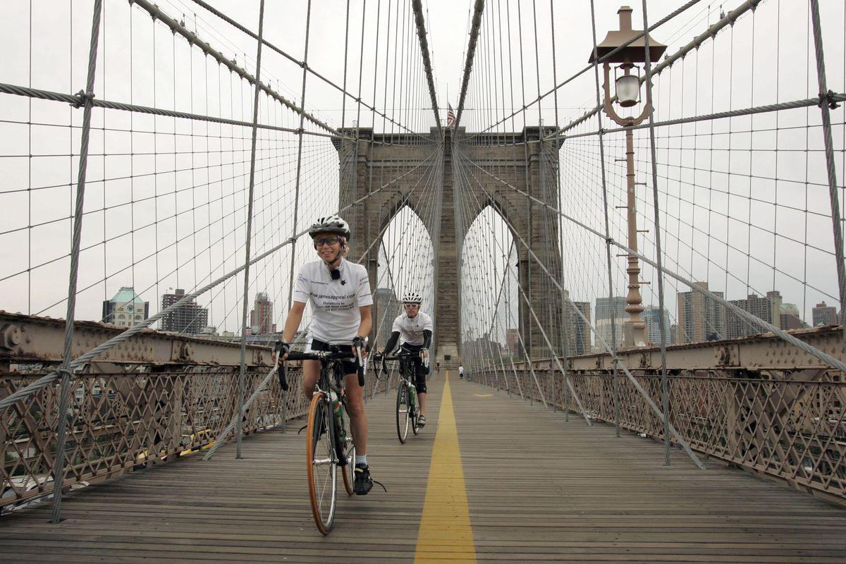 Bicyclists cross the Brooklyn Bridge.