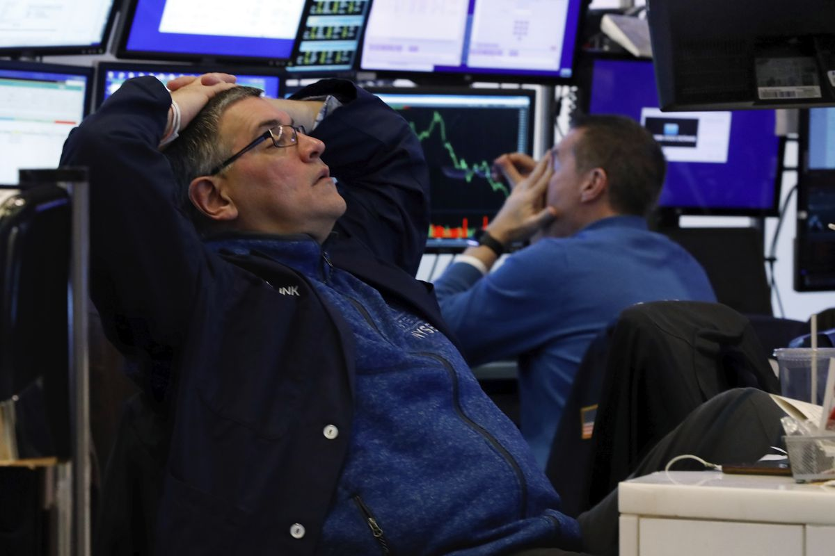 A pair of traders work in their booth on the floor of the New York Stock Exchange, Thursday, March 12, 2020.