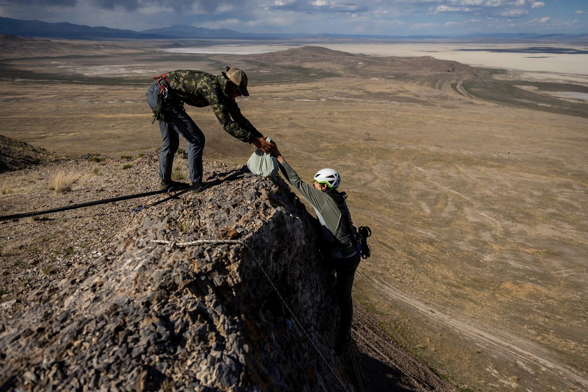Hawkwatch International research associate Dustin Maloney, right, hands a bagged golden eagle nestling to field biologist Jayden Skelly after Maloney removed it from its nest on a cliff in a remote area of Box Elder County on Wednesday, May 19, 2021.