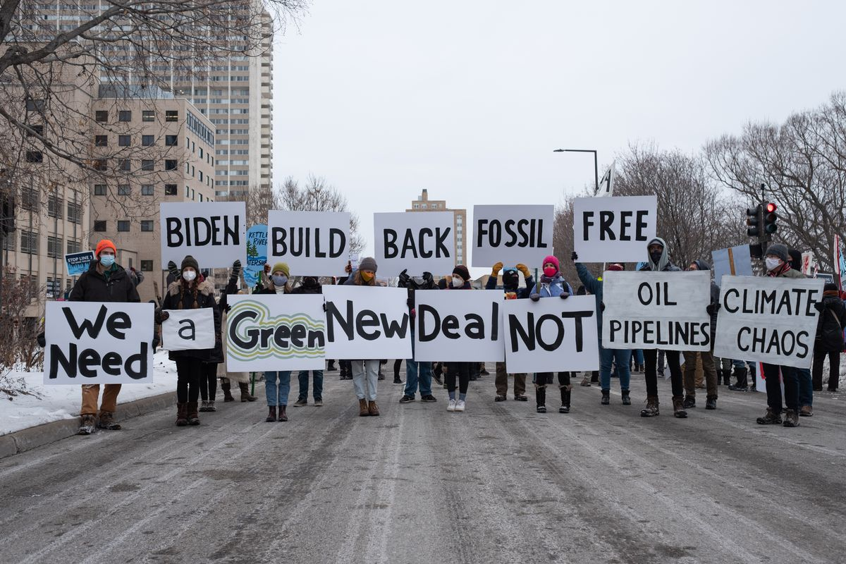 A group of climate activists is standing in the middle of the street on a winter's day in St. Paul, Minnesota. Each person is holding a sign with a different word. Collectively the signs read: Biden build back fossil free. We need a Green New Deal not Oil Pipelines. Climate chaos.