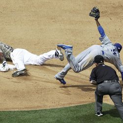 San Diego Padres' Cameron Maybin, left, steals second base as Los Angeles Dodgers shortstop Dee Gordon jumps clear in the fourth inning during a baseball game Sunday, April 8, 2012, in San Diego.