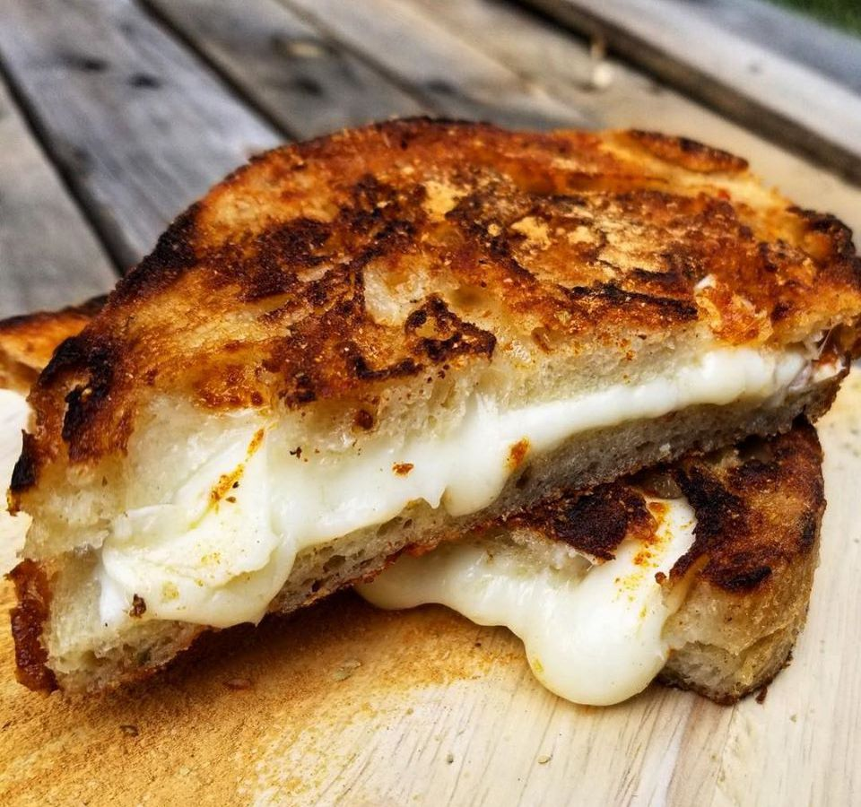 Closeup on a grilled cheese sandwich on a wooden picnic table