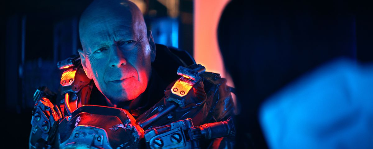 Bald Bruce Willis, generically scowling in blue and red light in Cosmic Sin