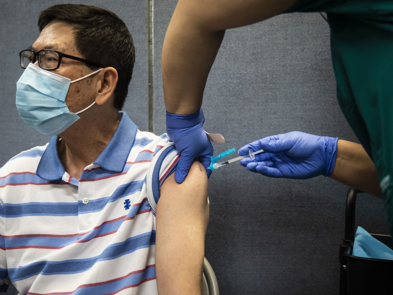 A person receives a COVID-19 vaccine earlier this summer in Chinatown. Infections are at a four-month high across Illinois.