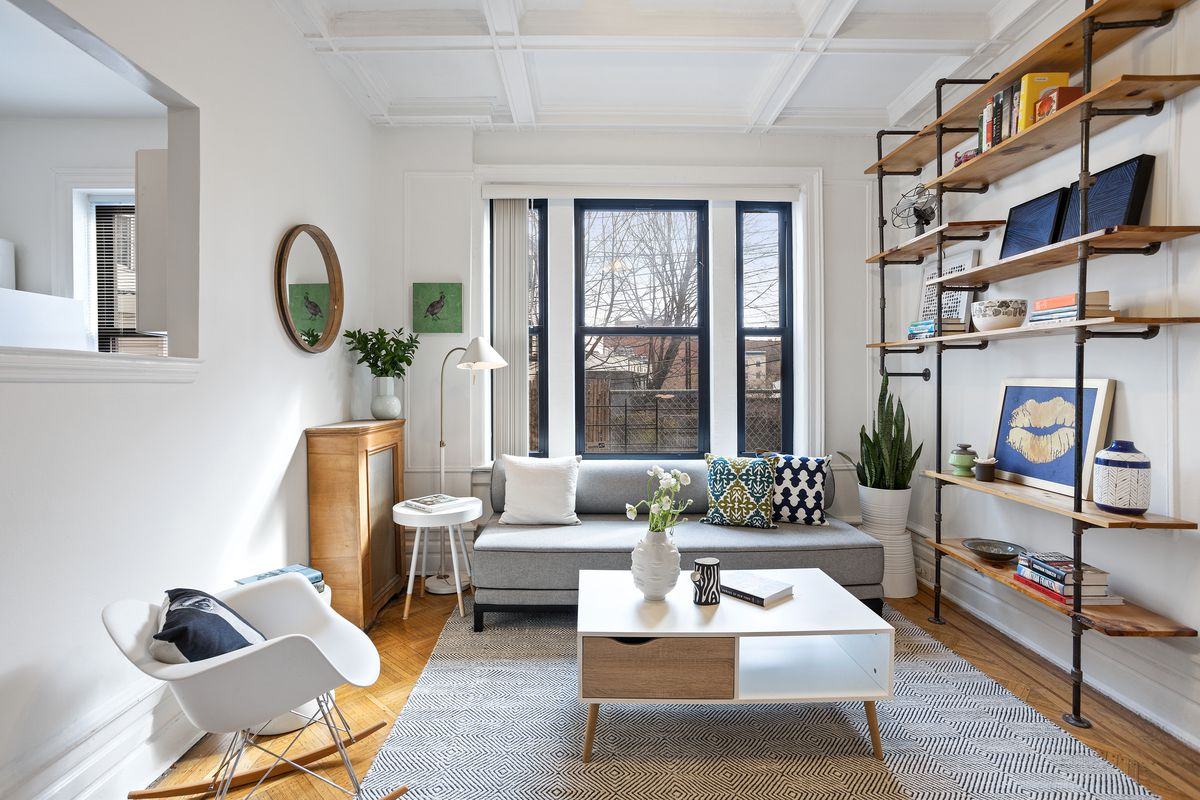 A living area with three windows, coffered ceilings, a grey couch, and a wooden coffee table.