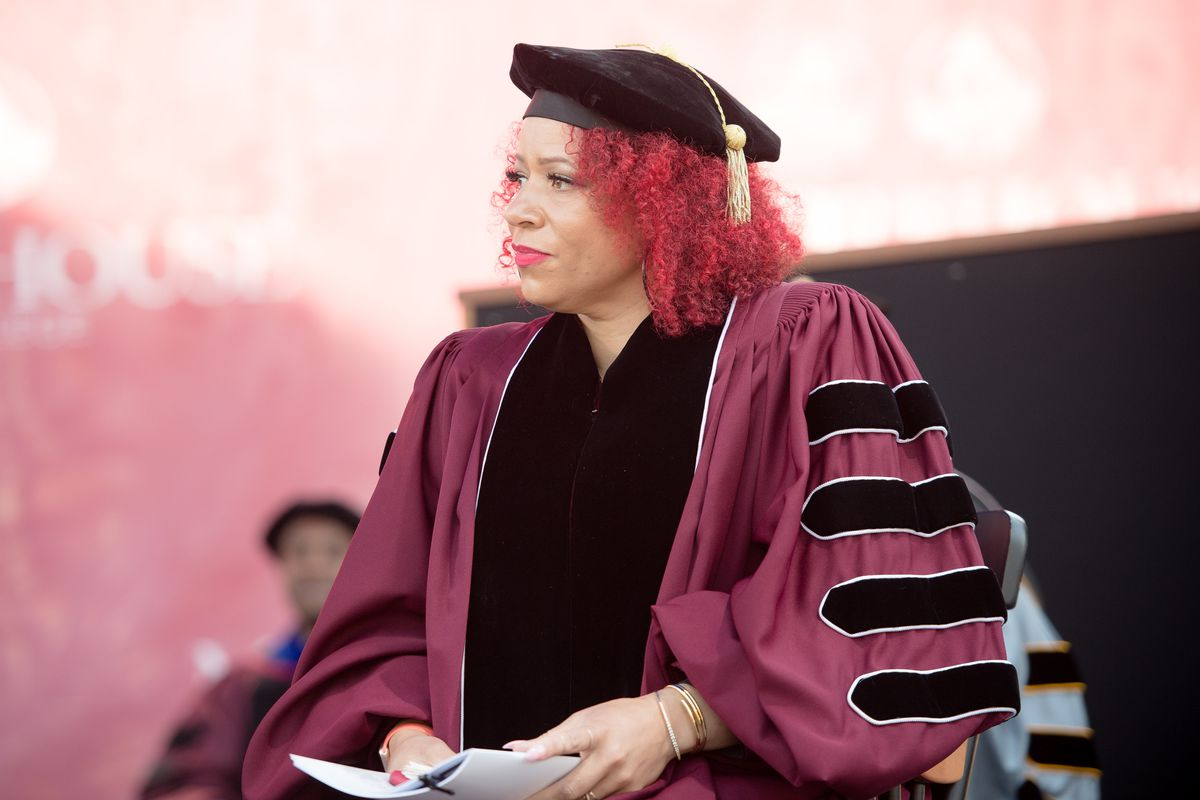 Nikole Hannah-Jones, wearing maroon and black graduation attire, sits on a stage during a Morehouse College commencement.