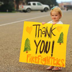 Kylie Walter holds a sign as she and other kids wait for fire crews to return from fighting the Brian Head Fire near the town of Panguitch on Tuesday, June 27, 2017.