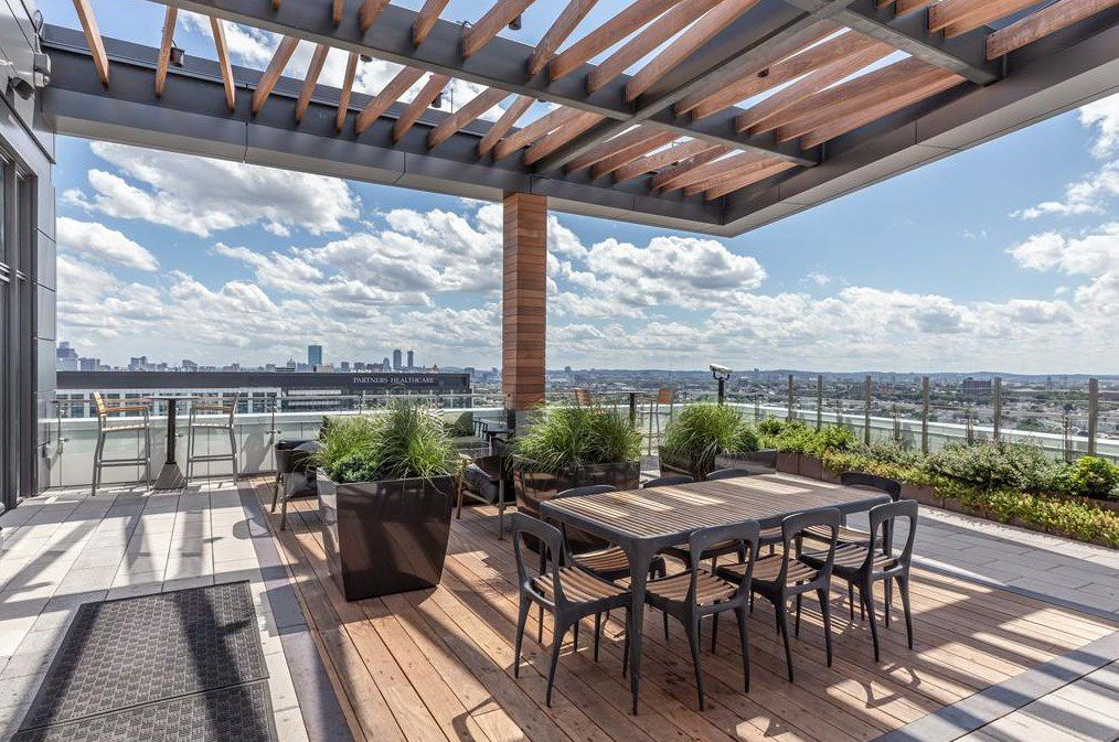 An expansive roof deck with a table and chairs, and there's a city's skyline in the distance.