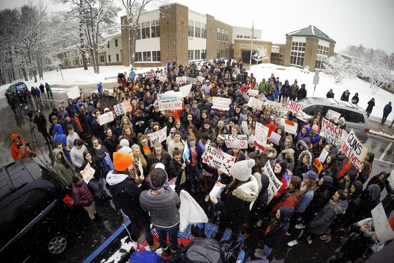 Students at Yarmouth High School participate in a walkout to protest gun violence, Wednesday, March 14, 2018, in Yarmouth, Maine. Leaders of the rally address the crowd from the back of a pick-up truck in front of the school. Yarmouth is one of the few sc