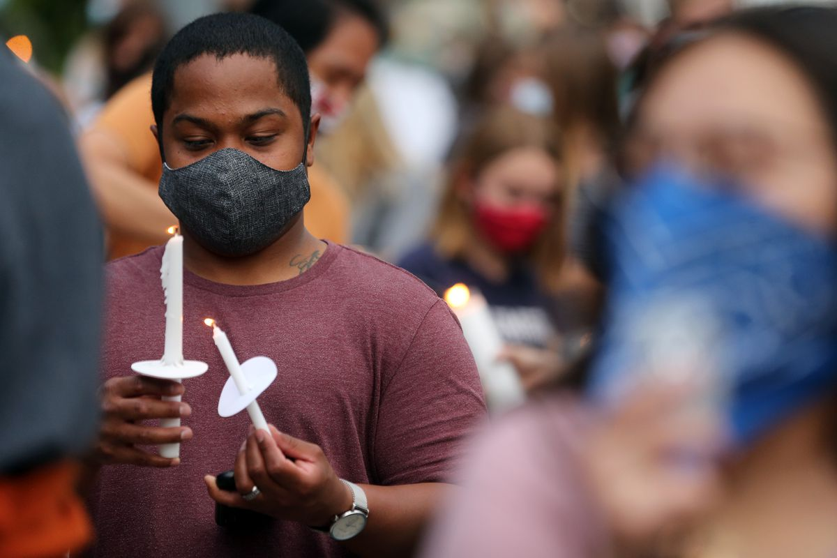 A young man protects his candle flame as he and over 1,000 people gather at the Provo Police Department on Friday, June 5, 2020, for a vigil organized by Unified Allies 4 Change for all those who have lost their lives to police brutality.