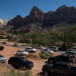 """Cars park in a dirt turnoff near the entrance to Zion National Park in Springdale on Thursday, Sept. 15, 2016.  """"Traffic and parking are not a problem absolutely every day,"""" Springdale Mayor Stan Smith said. """"But when it is a problem, it absolutely is a problem."""""""