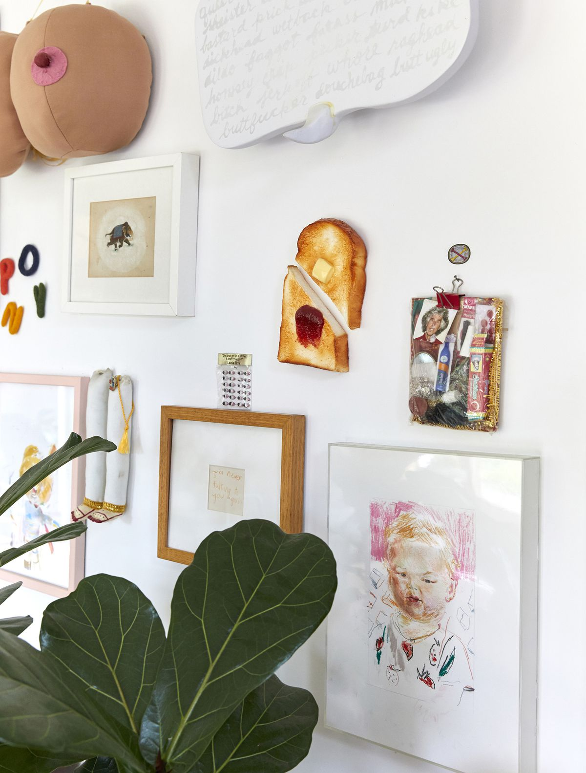 Various pieces of artwork on a painted white wall. There is a large houseplant sitting on the floor against the wall.