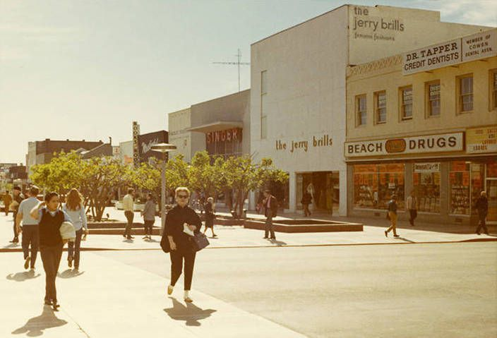 """Vintage photo of people shopping on a downtown street. The signs on the front of the businesses read """"Beach Drugs,"""" """"The Jerry Brills,"""" and """"Singer."""""""