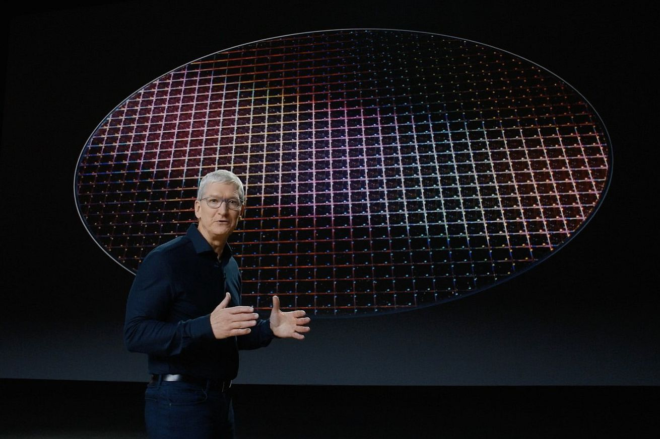 Apple CEO Tim Cook in front of a silicon wafer platter