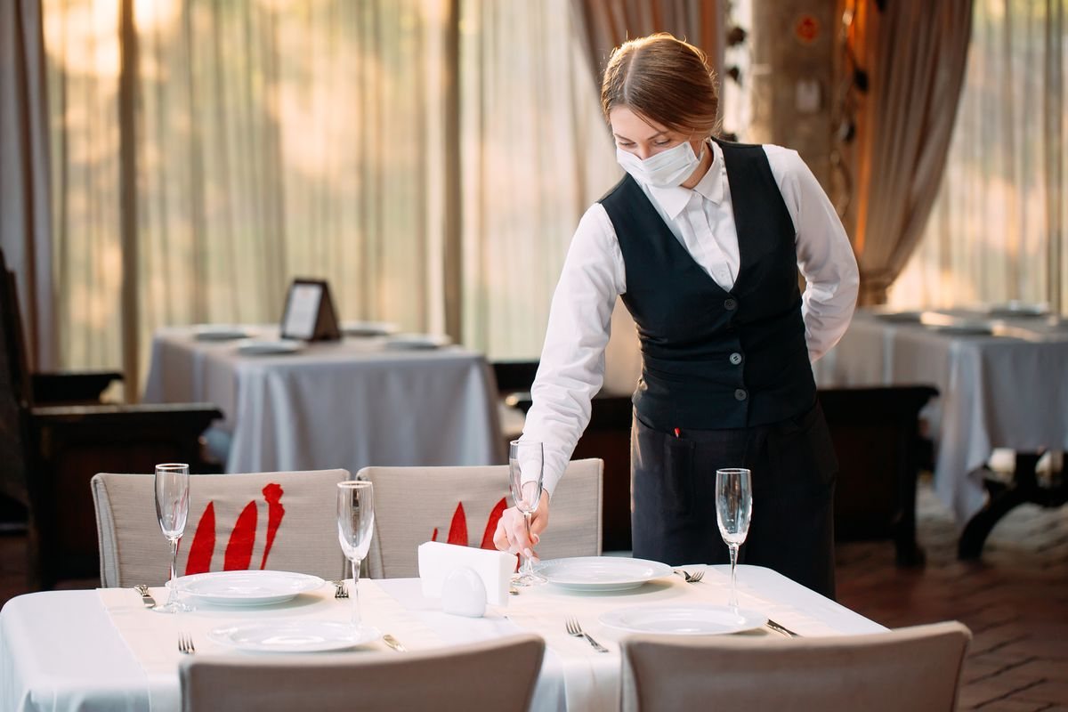 A restaurant server wearing a mask places a table setting on a table in an empty dining room