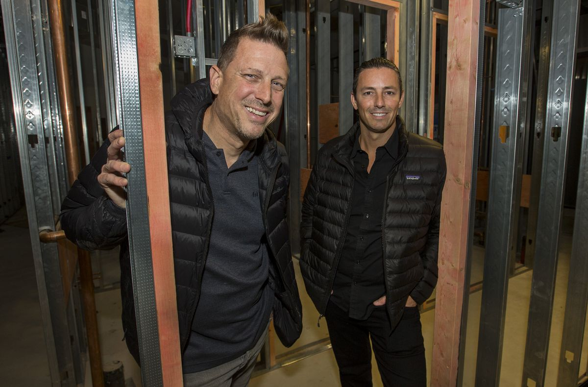 The chef and general manager pose around steel beams in a different part of their under-construction restaurant.