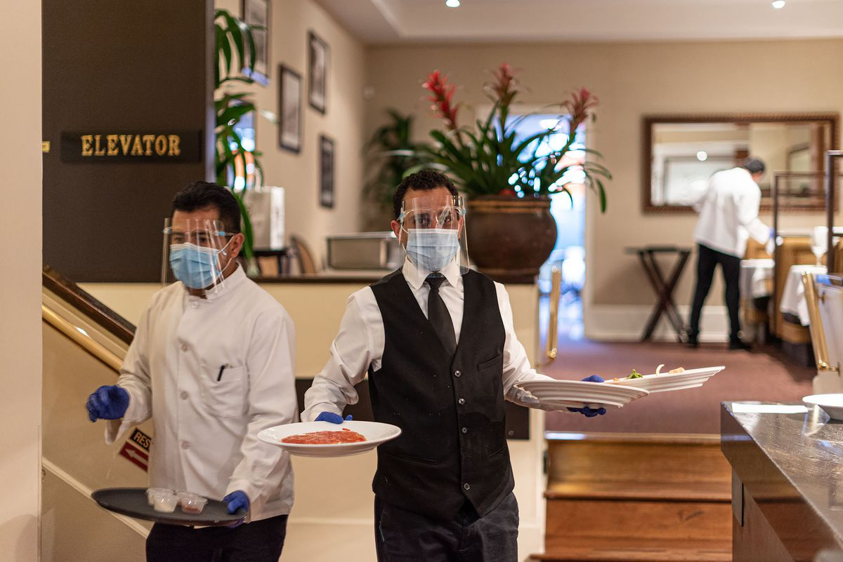 Workers handing out plates in suits inside of a restaurant, while wearing masks.