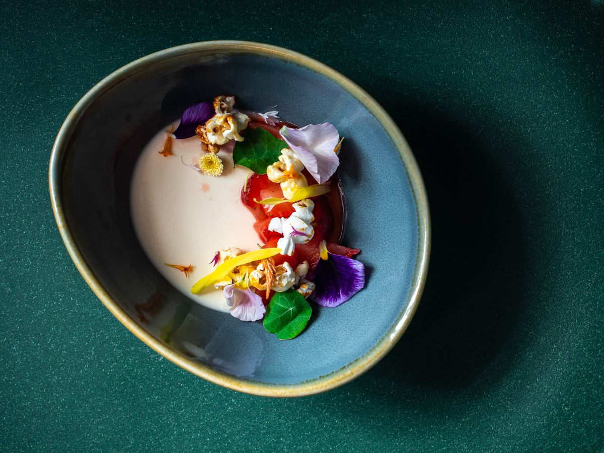 A bowl of creamy corn soup garnished with flowers and popcorn