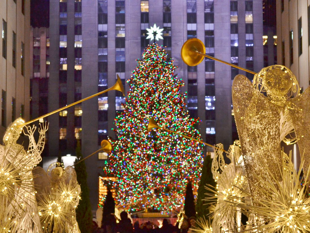 The Rockefeller Center Christmas tree. The tree is decorated with lights. There are illuminated statues of angels with trumpets in front of the tree.